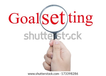 Hand Showing Goal setting Word Through Magnifying Glass   - stock photo