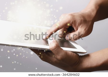 Hand showing gold color magic stars light on tablet