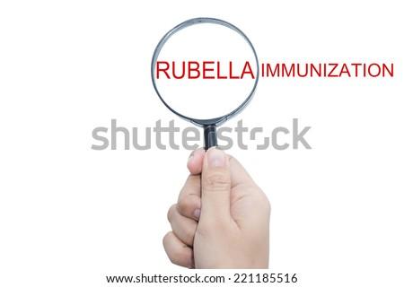 Hand Showing RUBELLA IMMUNIZATION Word Through Magnifying Glass - stock photo
