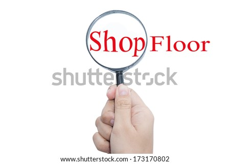 Hand Showing Shop Floor Word Through Magnifying Glass   - stock photo