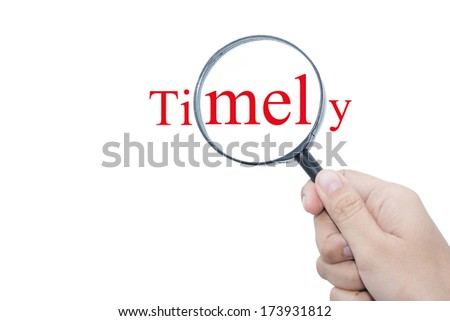 Hand Showing Timely Word Through Magnifying Glass   - stock photo