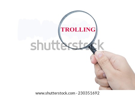 Hand Showing TROLLING Word Through Magnifying Glass  - stock photo