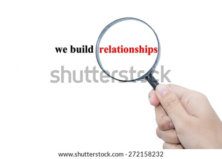 Hand Showing we build relationships Word Through Magnifying Glass  - stock photo
