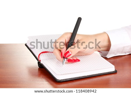 Hand signing in notebook  on wooden table isolated on white
