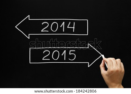 Hand sketching New year concept with white chalk on a blackboard. Going ahead to year 2015 and leaving the year 2014 behind. - stock photo