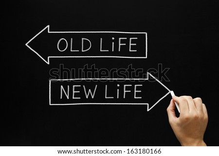 Hand sketching Old Life or New Life concept with white chalk on a blackboard.