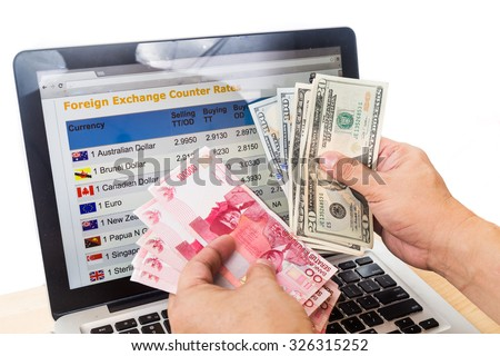 Hand sorting Indonesia Rupiah and US Dollar in front of currency exchange chart on computer screen. - stock photo