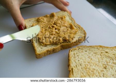 Hand spreading peanut butter on toast - stock photo