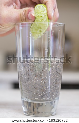Hand squeezes lime extracting juice into glass of water and chia seed - stock photo