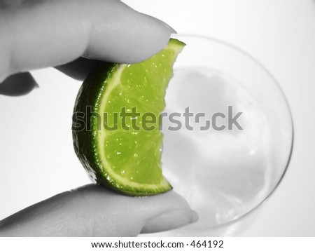 hand squeezing lime wedge into cool drink - stock photo