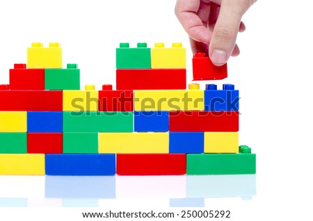 hand stack up lego set as a wall on white background - stock photo