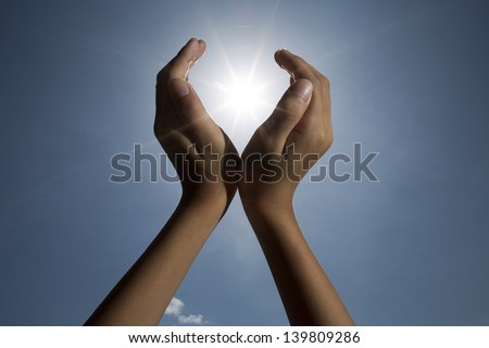hand sun and blue sky / hand sun and blue sky showing freedom or solar power concept  - stock photo
