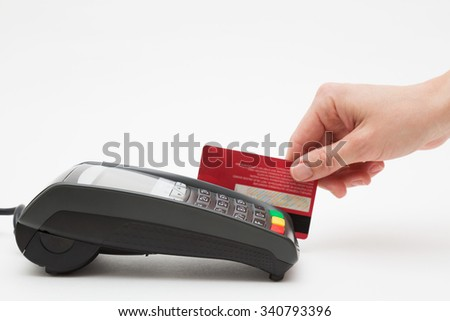 Hand swipe red credit through payment terminal  - stock photo