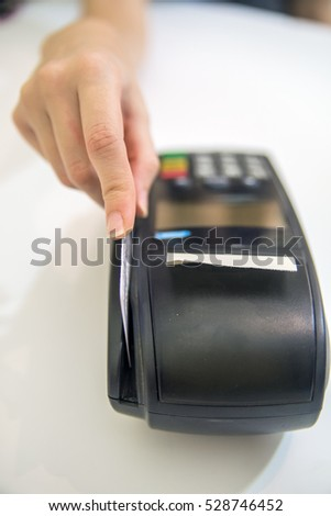 Hand swipe red credit through payment terminal. Debit card swiping on pos terminal. credit card reader machine on white background