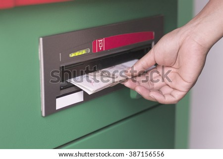 Hand take cash out from green ATM - stock photo