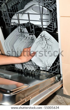 hand takes a plate from the open dishwasher - stock photo