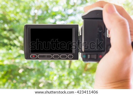 Hand taking blank black screen video camcorder  with bokeh green tree bush nature background, shooting video by mini camcorder  - stock photo