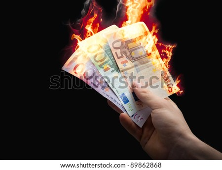 hand taking burning euro on a black background - stock photo