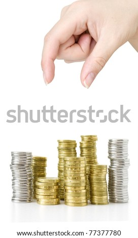 hand taking coin and stacks gold and silver isolated on white - stock photo
