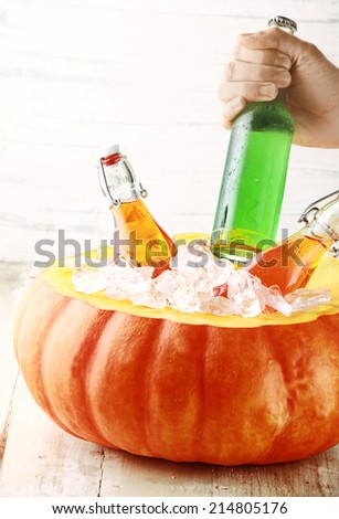 Hand Taking Cold Bottled Alcoholic Drink from Pumpkin Ice Bucket - stock photo