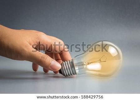 Hand taking light bulb as idea symbol - stock photo