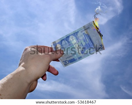 hand taking twenty burning euro on a blue sky background - stock photo