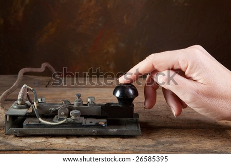 Hand tapping morse code on an antique telegraph - stock photo