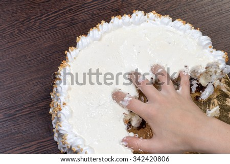 Hand tearing a large white cake - stock photo