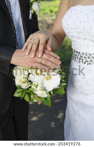 hand the bride and groom with rings on wedding bouquet