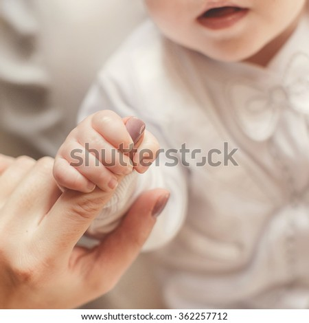hand the sleeping baby in the hand of mother close-up. Extreme closeup of a baby's hand in mother's finger. Close-up of baby's hand holding mother's finger. Close-up of baby's hand. tenderness