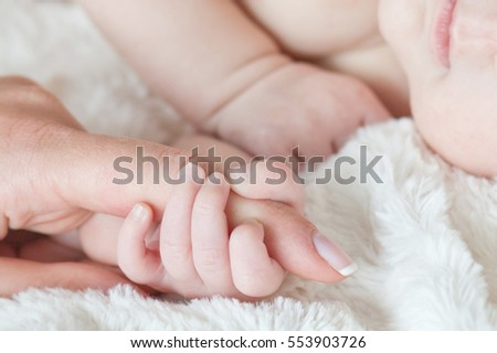 Hand the sleeping baby in the hand of mother close-up .Soft focus and blurry