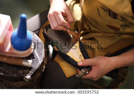 Hand thinning knife edge cut pieces of leather.Shoemaker performs shoes in the studio craft - stock photo