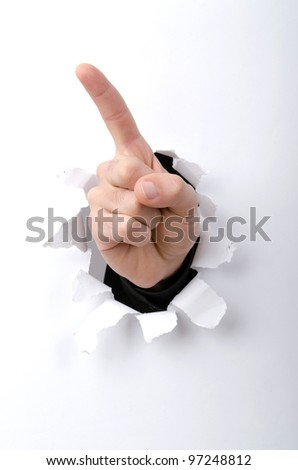 Hand through the hole in paper - stock photo