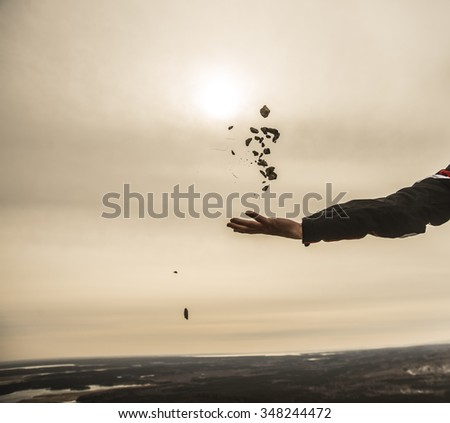 hand throw a lot  stones against sunset sky with clouds above horizon  - stock photo
