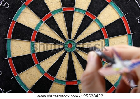 hand throwing dart to dartboard - stock photo
