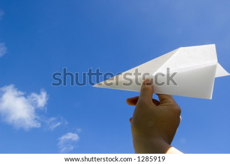 Hand throwing the paper airplane to the air - stock photo