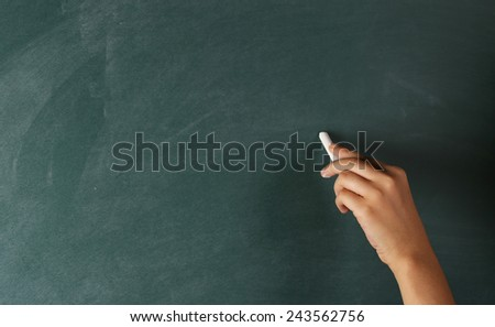 Hand to Draw Something on Blackboard with Chalk - stock photo