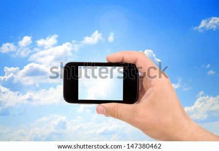 Hand to hold card, mobile phone, tablet PC on blue sky - stock photo