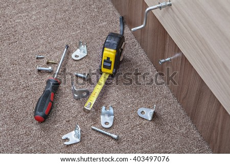 Hand tool, Screwed furniture screw, Screwdriver with screws and metal hinges, tape measure, all for assembling furniture. - stock photo