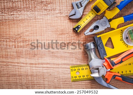 hand tools wrench tapline pliers level hammer nippers ruller on vintage wooden board with copyspace construction concept  - stock photo