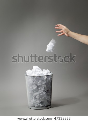 Hand tossing a crumpled paper in trash can. - stock photo