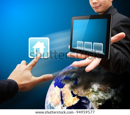 Hand touch house icon from tablet PC - stock photo