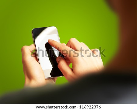 Hand Touch Mobile On Green Background - stock photo