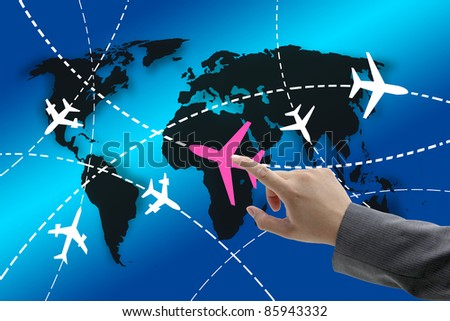 hand touch on planes with routes around the world for business travel concept - stock photo