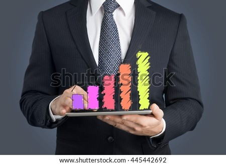 Hand touch screen graph on a tablet. - stock photo