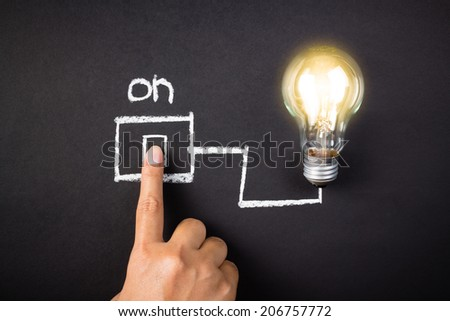 Hand touch the drawing switch with glowing light bulb
