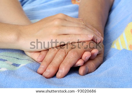Hand touches and holds an old wrinkled hand - stock photo