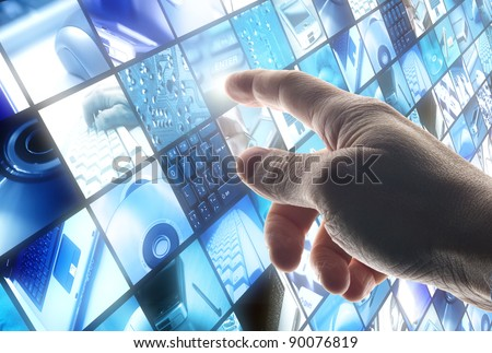 hand touching a wall of panels with technology images - stock photo
