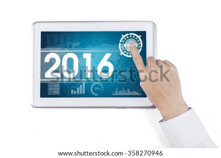 Hand touching digital tablet with the economic forecast for 2016 - stock photo