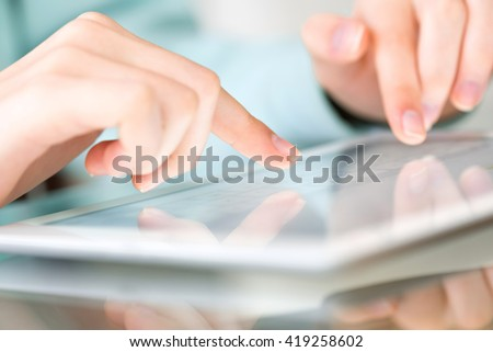 Hand touching screen on modern digital tablet pc.